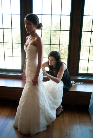 brides-mother-helps-her-fix-her-white-wedding-dress-before-her-ceremony