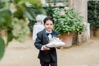 ring-bearer-in-tuxedo-carrying-pillow-with-flowers-on-top
