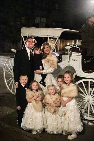 flower-girls-with-fur-wraps-ring-bearers-in-tuxedos-horse-drawn-carriage-at-wedding