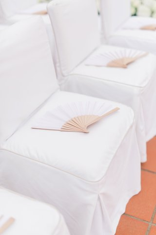 wedding-ceremony-with-chairs-with-white-covers-and-white-fans
