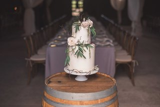 white-wedding-cake-with-fresh-flowers-leaves-and-branches