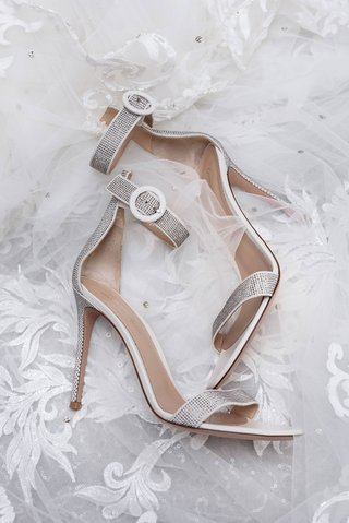wedding-shoes-on-veil-silver-high-heels-with-metallic-details-strap-at-ankle-and-toe-sandals