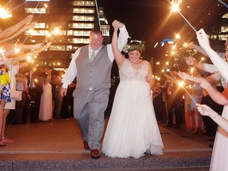 wedding-reception-grand-exit-bride-and-groom-hold-hands-sparkler-wand-exit-friends-and-family-city