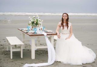 a-simple-blue-and-white-tablescape-on-a-white-and-brown-wooden-table-with-a-bride-on-a-beach