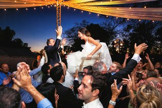 a-newlywed-couple-lifted-up-in-two-different-chairs-by-the-guests-at-their-reception
