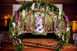 wedding-cake-on-swing-greenery-circle-arch-greenery-purple-flowers-white-flowers