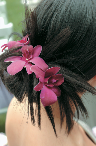 bridesmaid-bun-with-three-pink-and-purple-orchids-in-hair