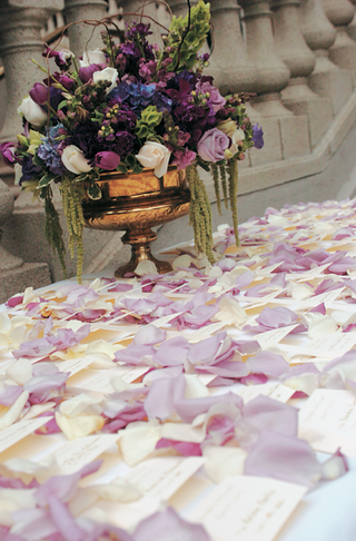escort-cards-on-table-sprinkled-with-flower-petals-and-urn-arrangement