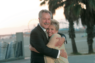 older-couple-smiles-in-front-of-beach-and-ferris-wheel