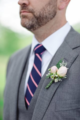 boutonniere-with-flower-buds-grey-suit-and-navy-tie-with-pink-stripes