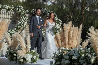 wedding-ceremony-bride-walking-down-aisle-with-father-of-bride-aisle-runner-pampas-grass-decorations
