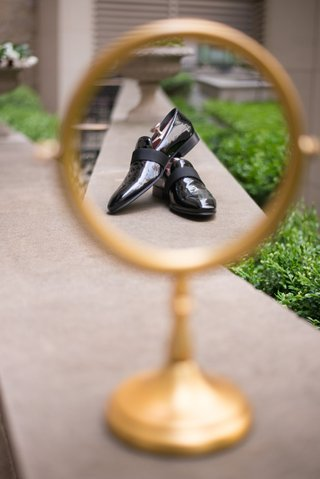gold-round-mirror-with-black-leather-shoes-in-reflection