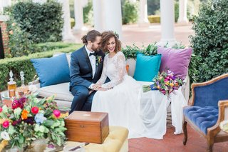 bride-and-groom-in-wedding-lounge-area-with-blue-purple-pillows-flower-arrangement