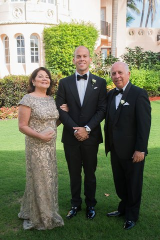 mother-of-groom-in-short-sleeve-gown-with-father-of-bride-in-tuxedo-groom-in-bow-tie