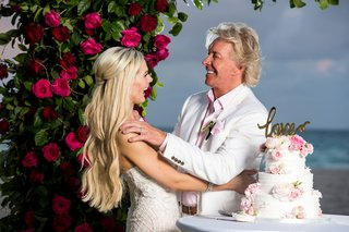 bride-and-groom-in-white-suit-jacket-under-ceremony-arch-cutting-into-white-cake-with-pink-flowers