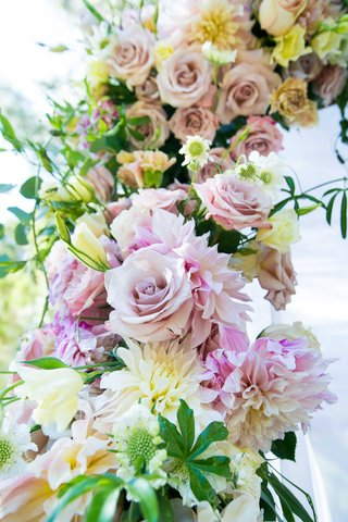 flowers-in-shades-of-blush-ivory-and-off-white-with-greenery-clinging-to-couples-outdoor-chuppah