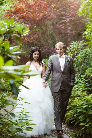 bride-and-groom-in-full-wedding-attire-walk-hand-in-hand-through-a-garden-during-their-first-look