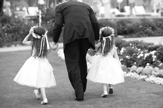 black-and-white-photo-of-flower-girls-walking-with-man-in-suit
