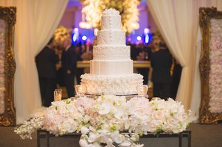 white-wedding-cake-with-rosettes-covering-one-layer-lace-design-on-others-surrounded-by-flowers