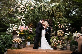 wedding-ceremony-wood-stage-greenery-white-blush-flowers-chuppah-first-kiss-jewish-ceremony-fall