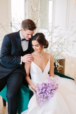 bride-in-hayley-paige-wedding-dress-bouquet-of-lavender-sweet-peas-velvet-green-chair