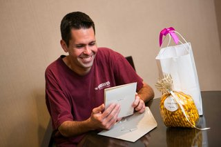 a-smiling-groom-reads-letter-from-his-bride-accompanied-by-a-gift