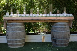 wedding-escort-cards-displayed-on-table-of-wine-barrels-candles-in-glass-hurricanes