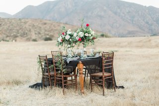 styled-shoot-tablescape-dark-motif-black-linen-tall-centerpieces-wood-chairs-outside-hills