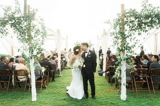 wedding-ceremony-bride-and-groom-kiss-arbor-over-ceremony-seating-greenery-wood