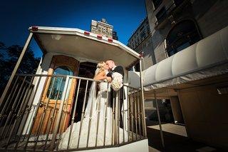 bride-in-vera-wang-groom-in-vera-wang-newlyweds-kiss-on-back-of-trolley-in-chicago