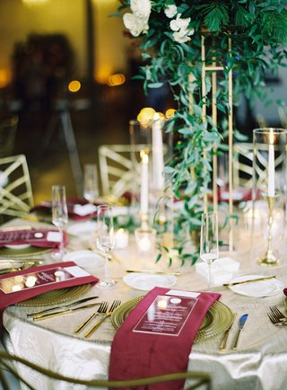 round-wedding-table-glass-top-ivory-linen-gold-flatware-charger-burgundy-napkin-gold-centerpiece
