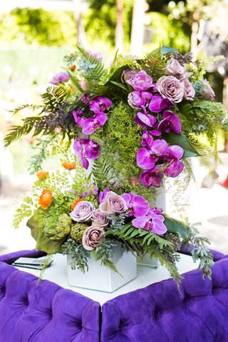 wedding-cocktail-hour-bright-purple-tufted-settee-furniture-orchid-rose-greenery-artichoke-flowers