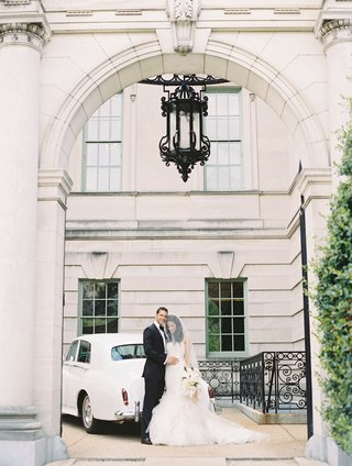 bride-and-groom-couple-wedding-portrait-in-arch-at-anderson-house-in-washington-dc-mermaid-gown