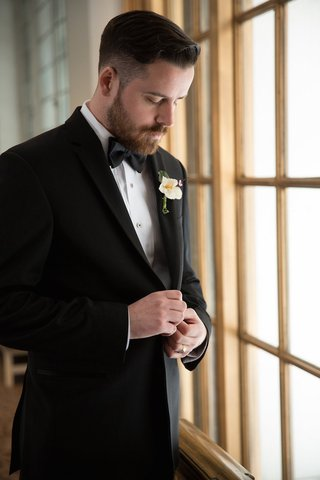 groom-looking-down-at-window-sill-in-black-tuxedo-and-bow-tie