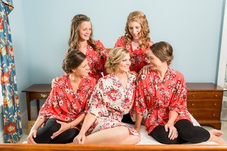 bride-in-white-pink-red-wedding-robe-with-bridesmaids-in-red-pink-flower-print-robes-on-bed-bridal