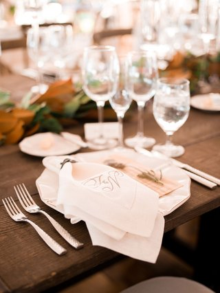 wood-table-with-no-linens-place-setting-white-plate-linen-napkin-monogram-magnolia-leaf-garland