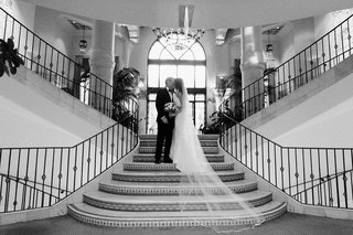 black-and-white-photo-of-bride-and-groom-kissing-on-the-stairs-of-casa-del-mar