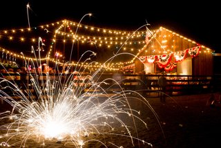 sparkler-on-ground-in-front-of-fourth-of-july-party-at-barn