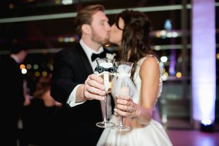 bride-and-groom-kiss-while-holding-out-champagne-glasses-decorated-with-bow-tie-and-tulle-his-hers