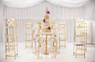 wedding-cake-on-gold-riser-with-gold-bookshelves-featuring-other-desserts-surrounding-it-orchids
