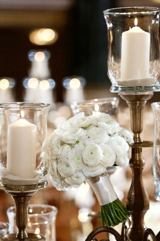 wedding-bouquet-next-to-candles-with-white-ranunculus-wrapped-with-ivory-ribbon