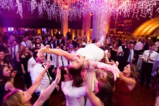 bride-in-second-wedding-dress-for-reception-on-back-crowd-surfing-at-reception-from-stage-dance-floo