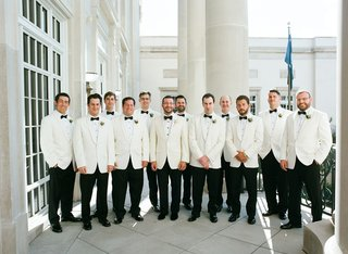 groom-and-groomsmen-with-white-tuxedo-jackets-black-pants-and-bow-ties-lily-of-the-valley