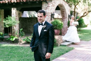 groom-in-black-tuxedo-waits-to-see-bride-in-a-strapless-hayley-paige-dress-with-tiered-skirt