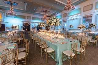 gold-chairs-around-long-table-with-blue-tablecloth