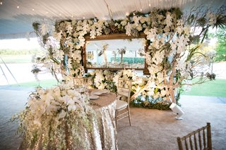 large-floral-wall-with-grapewood-white-orchids-and-hydrangeas-mirror-behind-sweetheart-table