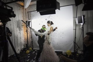 bride-in-a-strapless-mark-zunino-dress-with-groom-dressed-in-black-in-slow-motion-booth