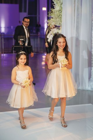 flower girl dresses in ivory holding pomander bouquet with ribbon open toe shoes purple lighting