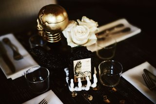 wedding-reception-skeleton-hand-holding-beware-sign-gold-skull-white-flowers