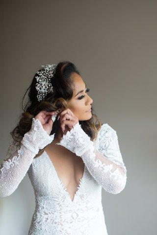 bride in plunging neckline wedding dress long sleeves putting on earrings sparkling headpiece hair